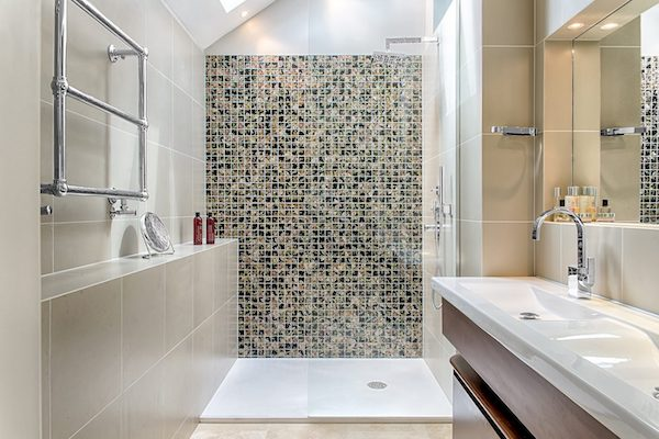 Bathroom with cream wall tiles and splashback with patterned tiles