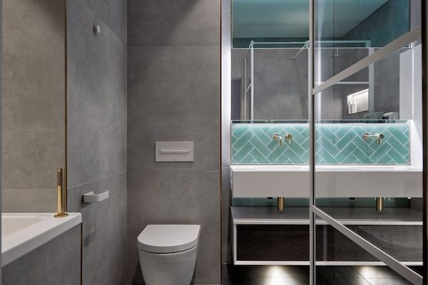 bathroom tiled with large grey ceramic tiles and green metro tiles in house located on Glenarm Road