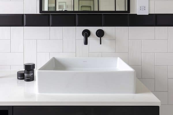 black and white metro tiles around white sink with black fixtures in house located at Osterley Road