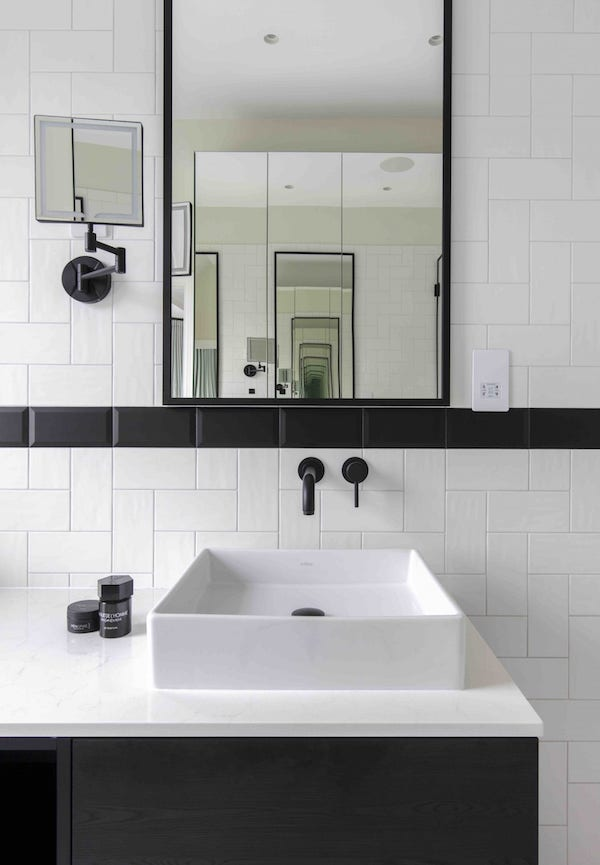 black sanitary ware in kitchen tiled with white and black metro tiles in house located on Osterley Road