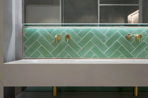 green metro tiles above wide white coloured sink with gold fixtures in house located on Glenarm Road