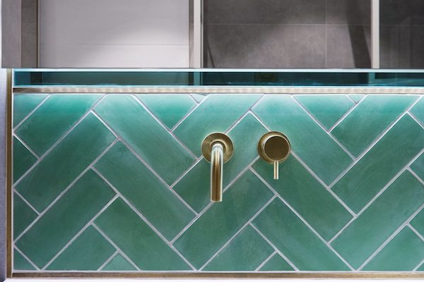 green metro tiles around bathroom sink with gold fixtures in home located on Glenarm Road