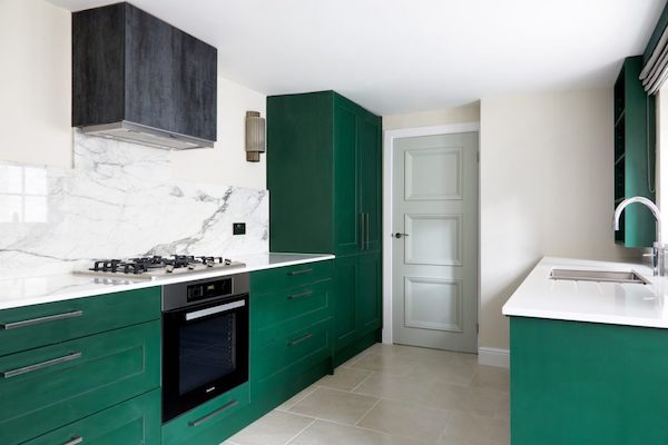 cream floor tiles in stylish kitchen with green cabinets