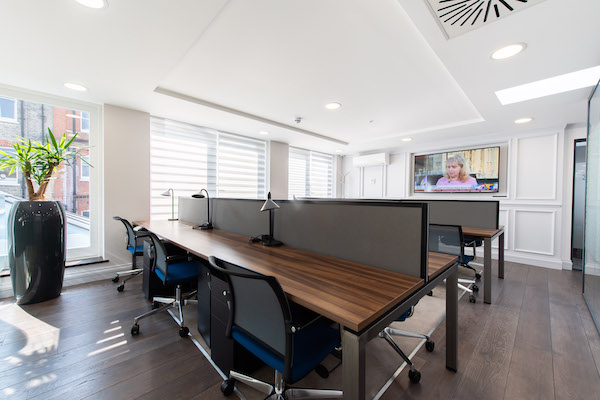 office work station with hard flooring and walls and ceilings painted white
