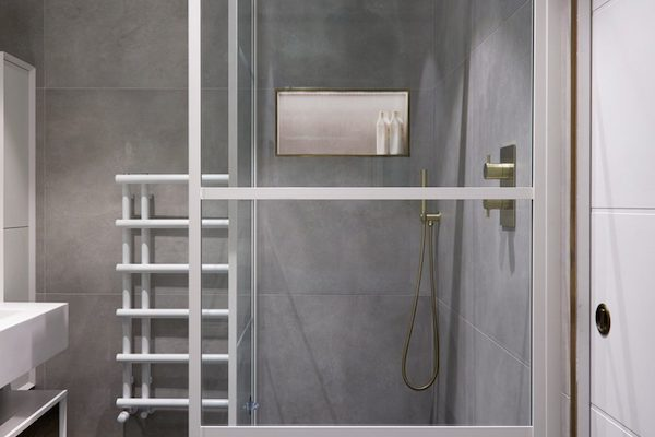 shower screen with white trim in front of shower tiled with large grey ceramic tiles in house located on Glenarm Road