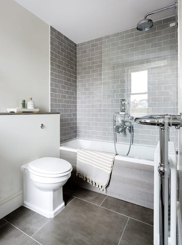 small bathroom tiled with large dark grey tiles for the floors and light grey tiles for walls
