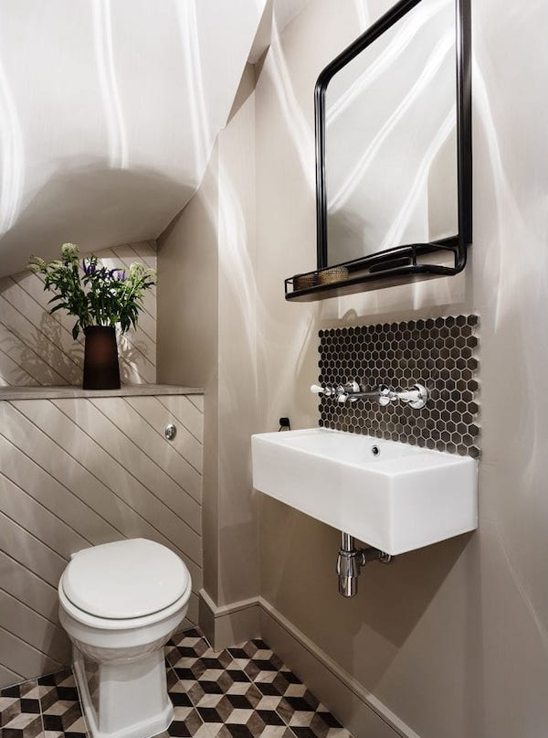 Patterned mosaics in small bathroom floor and geometric tiles for sink splashback